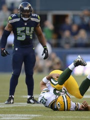 Green Bay Packers quarterback Aaron Rodgers (12) falls on his back as Seattle Seahawks linebacker Bobby Wagner (54) looks on during their Week 1 game at CenturyLink Field in Seattle.