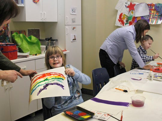 """Allie Hobbs, 12, of Webster, proudly shows off her finished """"feelings rainbow"""" she painted in her art therapy class at the Family Autism Center in Rochester."""