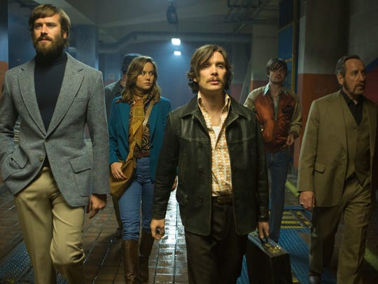 "The cast of (from left, Armie Hammer, Brie Larson, Cillian Murphy, Sam Riley, Michael Smiley) model the best of mid-1970s fashion on their way to a gun deal in ""Free Fire."""