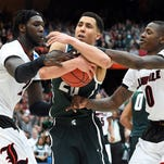 Michigan State guard Travis Trice (20) grabs a loose ball against Louisville forward Montrezl Harrell (24) and guard Terry Rozier (0) during overtime in the finals of the east regional of the 2015 NCAA Tournament on Sunday at Carrier Dome in Syracuse, N.Y.