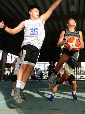 The Under-16 Inarajan Hawks' Jovin Terlaje attempts a layup with Crusaders Black's Illac Lalic playing defense in a recent 2018 Sinajana Youth Basketball League at the Sinajana Gym.