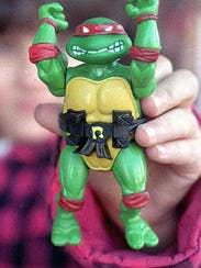 """An unidentified girl holds """"Raphael"""", one of the four Teenage Mutant Ninja Turtles in Boston, Dec. 12, 1998. The turtles were created by Peter Laird and Kevin Eastman."""