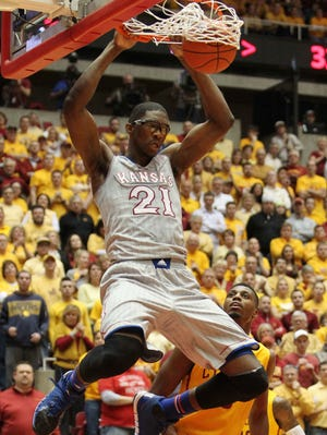 Joel Embiid dunks home two of his 16 points for Kansas.