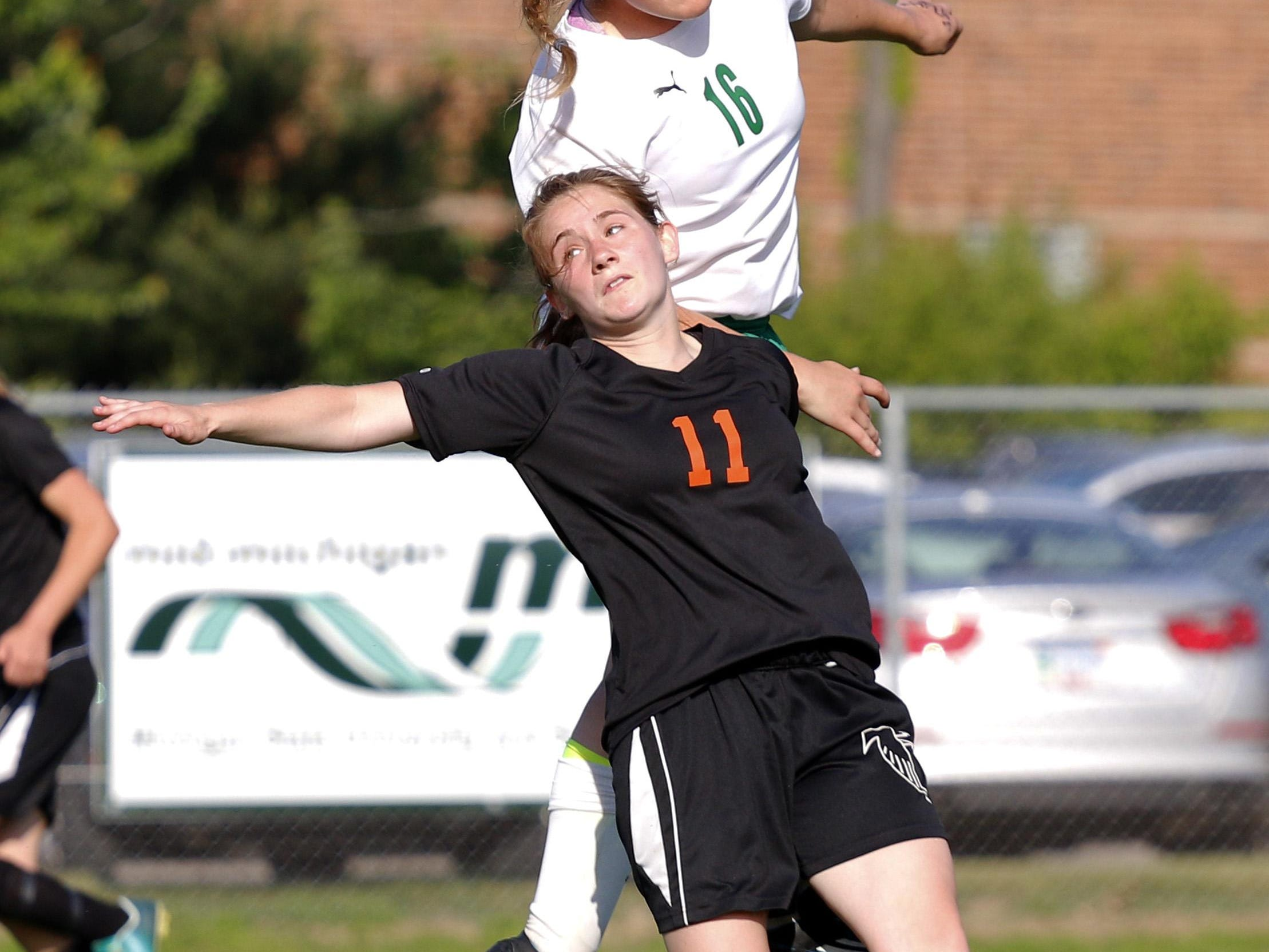 Leslie's Madison Willsey (11) and Jackson Lumen Christi's Megan Saunders (16) vie for a header in their soccer regional game, Wednesday, June 3, 2015, in Williamston, Mich.