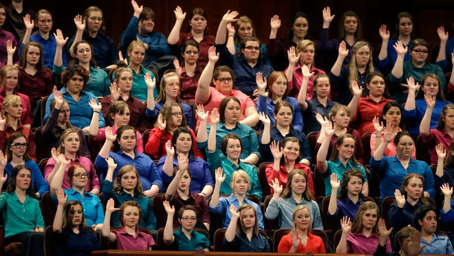 In this April 2, 2016, file photo, members of the combined choir from BYU-Idaho raise their hands during a sustaining vote at the two-day LDS church conference in Salt Lake City. Latter-Day Saints gather for a twice-yearly conference to hear spiritual guidance from top leaders during a testy presidential election and as society grapples with issues of race and sexuality.