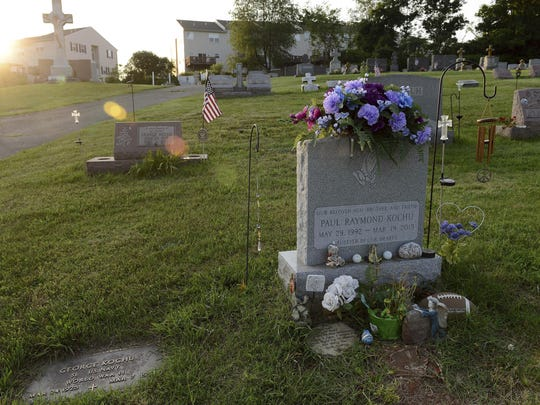 In this Tuesday, June 13, 2017, the gravesite of Paul Kochu, foreground, sits amongst other graves at a cemetery in Pottstown, Pa. (Rebecca Droke/Pittsburgh Post-Gazette via AP