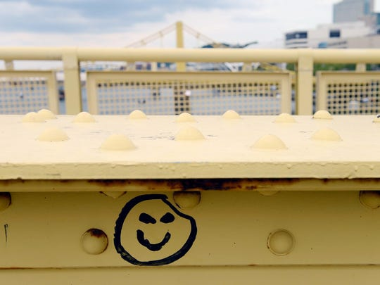 In this Wednesday, Sept. 6, 2017 photo, a smiley face seen drawn on the Sixth Street Bridge in Pittsburgh, Pa., is thought by some to be related to a series of serial killings in the area. (Rebecca Droke/Pittsburgh Post-Gazette via AP)