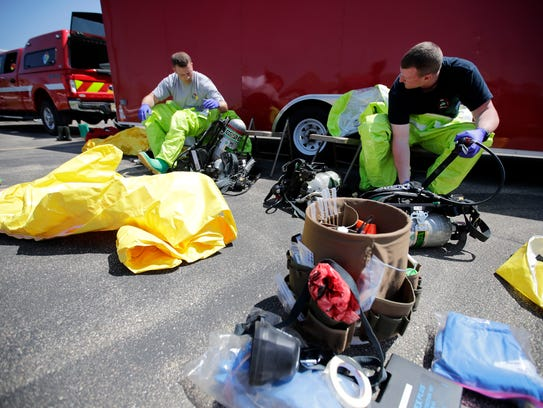 Appleton firefighters prepare their hazmat suits Tuesday