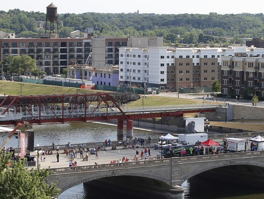 RAGBRAI riders begin to fill the Court Avenue bridge during an overnight stop in Des Moines in 2013. The Principal Riverwalk Red Bridge is pictured in the background.