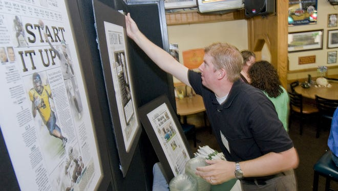 LSJ Sports Columnist Joe Rexrode helps set up reprints of the LSJ front page during the celebration for the new greenandwhite.com September 17, 2008 at Reno's East in East Lansing.  KEVIN W. FOWLER PHOTO  Photo Gallery