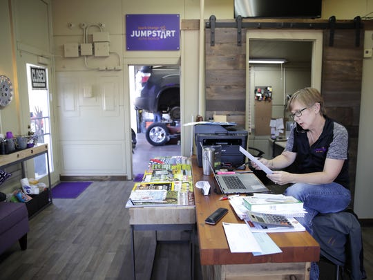 Katie VanderWielen, general manager with JumpStart Auto Repair in Neenah, takes a phone call at the shop.