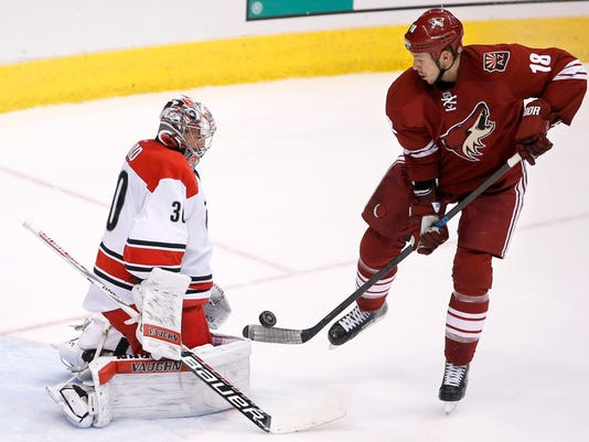 Carolina Hurricanes' Cam Ward (30) makes a save on a shot by Arizona Coyotes' David Moss (18) during the third period of an NHL hockey game Thursday, Feb. 5, 2015, in Glendale, Ariz.  The Hurricanes defeated the Coyotes 2-1 in a shootout. (AP Photo/Ross D. Franklin)