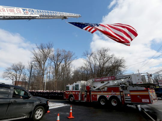 A FDNY truck drives under a flag hanging from a Hugh