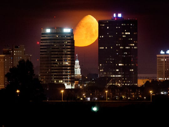 A waxing gibbous moon sets over the downtown Knoxville