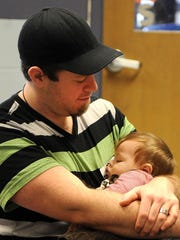 Blake Kennard holds his 10-month-old son, Griffin, Saturday morning during a free boot camp for new dads program at the Mansfield YMCA.