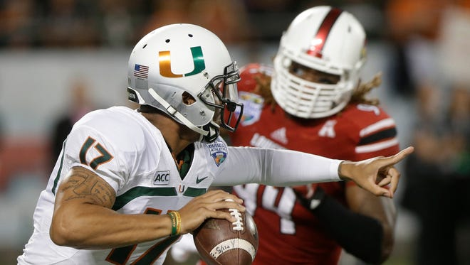 Former Miami quarterback Stephen Morris scrambles away from Louisville defensive end Lorenzo Mauldin during the first half of the Russell Athletic Bowl