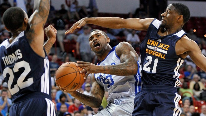 The Sixers' Sean Kilpatrick shoots between the Jazz's Malcolm Thomas (22) and Ian Clark during an NBA summer league basketball game Saturday in Las Vegas.