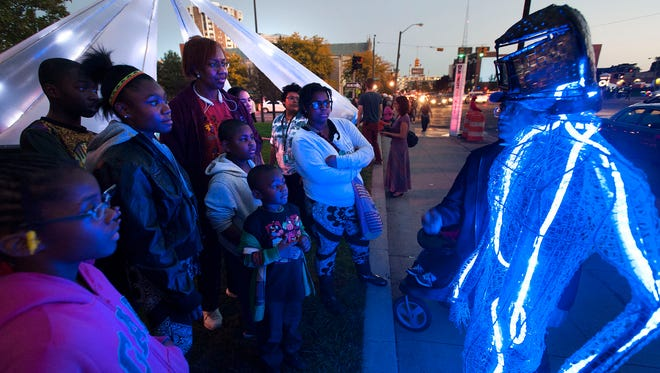 Rick Cronn of Ann Arbor shows a crowd his UR Video Head sculpture at Woodward and Warren during Dlectricity in Detroit on Friday. In the background is an electromechanical light sculpture.