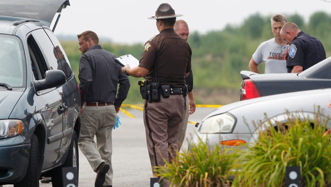 Police collect information at the scene following a shooting in the parking lot of Jordan Manufacturing Tuesday, August 5, 2014, at 1200 S. Sixth in Monticello. According to White County Sheriff Patrick Shafer, police found a man with a handgun dead in the parking lot shortly before noon. A second man was found dead in a car in the parking lot. A woman found in the passenger seat of the car was transported to IU Health White Memorial Hospital, where she was pronounced dead.