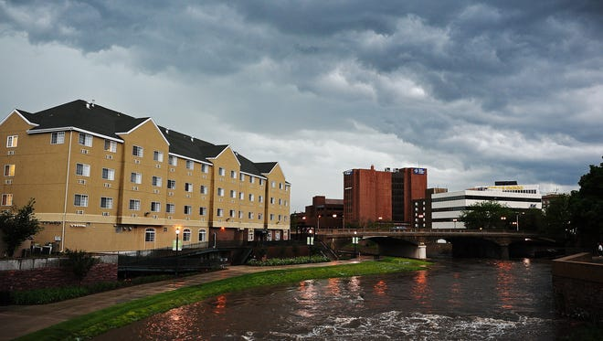 Storm clouds on Monday, June 16, 2014, over the Big Sioux River in downtown Sioux Falls, S.D.