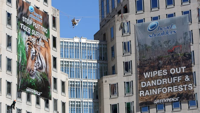 Greenpeace activists rappel and hang banners off Procter & Gamble's headquarters in Cincinnati on Tuesday, March 4, 2014.
