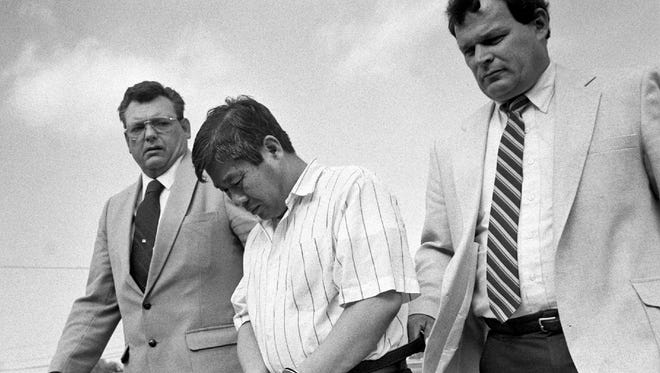 In a Sept. 6, 1989, file photo, Han Tak Lee is lead to the Swiftwater, Pa., State Police barracks for processing with State Police Fire Marshall Thomas Jones, right, and Stroud Township Police Investigator Vernon Bortz. Lee is serving a life sentence for murder and arson for setting a fire in 1989 at a church retreat cabin in Stroudsburg, Pa., in which his daughter died. In June 2014, U.S. District Judge Martin Carlson concluded the science underlying Han Tak Leeís conviction in northeastern Pennsylvania was wrong. Judge Carlson is recommending that Lee either be given a new trial or released from prison.   (AP Photo/The Pocono Record, David W. Coulter, File) MANDATORY CREDIT  ORG XMIT: PASTR502