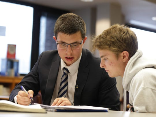 North Central High School senior Stefan Stoykov (left) tutors fellow student Abe Lahr in the school library.