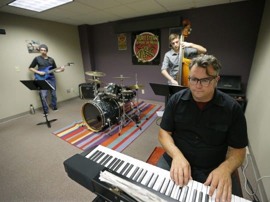Kurt Stein, bottom right, practices jazz standards for an upcoming gig with student interns Tor Swanson, left, and Zach Monka at Kurt Stein's School of Music in Neenah. The nonprofit school opened in September.