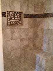 This shows a picture-framed wall niche in a mosaic and the use of the same mosaic in another size as a band around the shower.