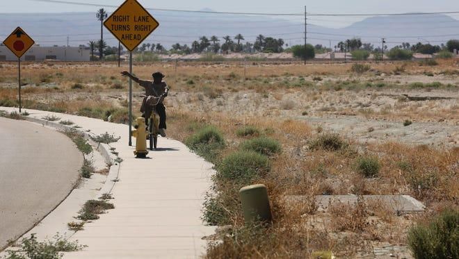 A man rides his bike next to the proposed site of an orthopedic joint center in Indio. The city this week withdrew approval of the project, caving to opposition from the California Pilots Association. File photo.