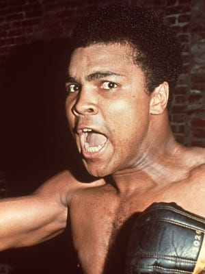 circa 1963:  Headshot of American boxer Muhammad Ali, former World Heavyweight Champion, shouting while wearing boxing gloves.  (Photo by Hulton Archive/Getty Images)