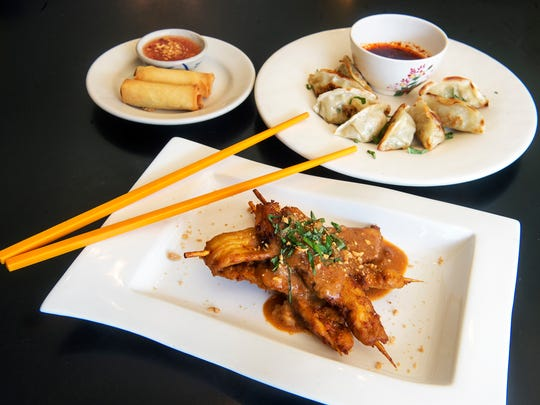 Chicken satay, foreground, vegetable egg rolls with sweet chili sauce, back left, and vegetable dumplings with ginger soy sauce, back right.