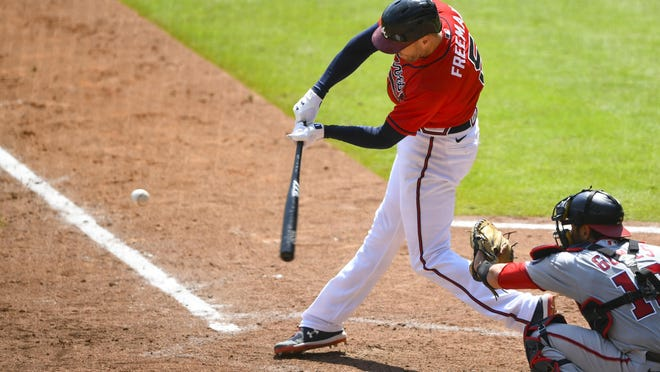 Atlanta Braves' Freddie Freeman connects for a grand slam over left center field during the sixth inning of a baseball game against the Washington Nationals, Sunday, Sept. 6, 2020, in Atlanta.