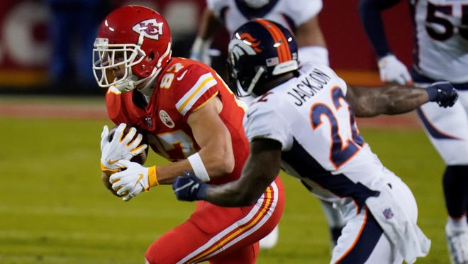 Kansas City Chiefs tight end Travis Kelce (87) runs after a catch as Denver Broncos strong safety Kareem Jackson (22) defends during Sunday night's game at Arrowhead Stadium.