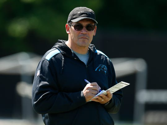 """FILE - This May 16, 2014, file photo, shows Carolina Panthers head coach Ron Rivera looking on at his players during an NFL football rookie minicamp in Charlotte, N.C. Rivera and quarterback Cam Newton seem more focused on the big picture: getting the Panthers to the playoffs in back-to-back seasons for the first time, and winning a postseason game for the first time since 2005. """"Status quo isn't good enough,"""" Rivera said. (AP Photo/Chris Keane, File)"""