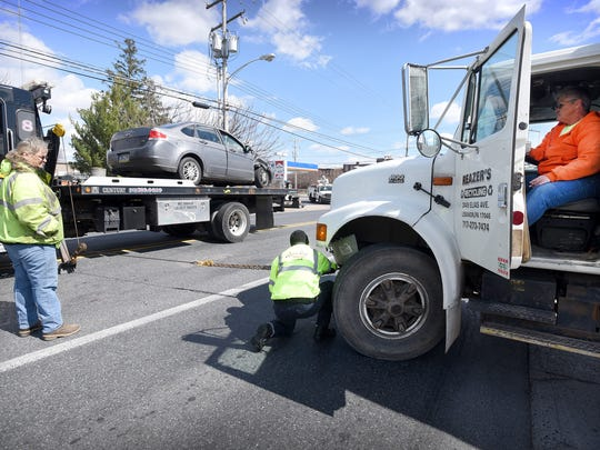 A tow truck pulls the bumper from a garbage truck out