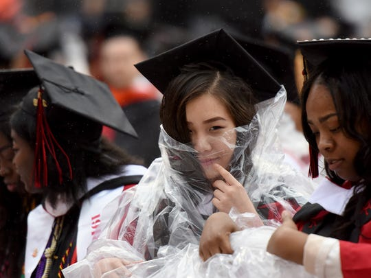 The 252nd commencement of Rutgers University was held at High Point Solutions Stadium in Piscataway on Sunday, May 13, 2018. Students pull on ponchos as rain begins to fall during graduation.