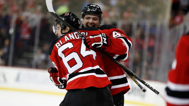 New Jersey Devils left wing Joseph Blandisi (64) and center John Quenneville (42) celebrate Quenneville's firs career goal during the second period of an NHL hockey game against the New York Rangers, Tuesday, March 21, 2017, in Newark, N.J. (AP Photo/Julio Cortez)