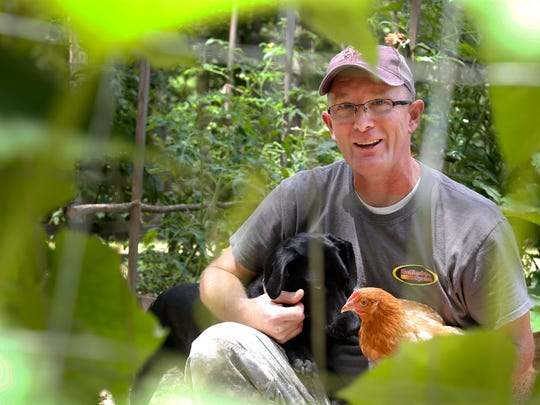 Bo Sandifer holds his dog, Addie, and one of his seven hens while sitting in his garden at his home in Brandon Friday. Bo uses the chicken manure to fertilize his family's garden.