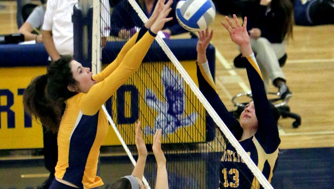 Hartland's Sarah Skinner, left, blocks South Lyon's Brooke Campos during Wednesday night's district semifinals. The Eagles took the Lions in four games to reach the district championship game for a second straight year.