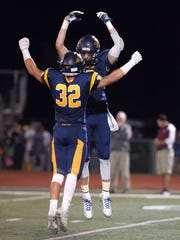 Victor's Andrew Russell, facing, and Tommy Ryan (32) celebrate their win over Aquinas.