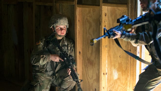 In this Oct. 4, 2017, photo, U.S. Army recruit Kirsten practices building clearing tactics with male recruits at Ft. Benning, Ga. She is one of a handful of women training to become infantry soldiers. Conservatives are advocating for military spending to be separated from short-term spending bills.