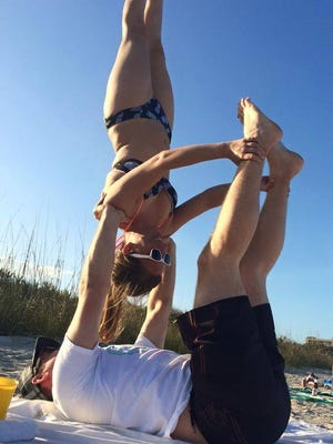 Kyle and Justin Lieneck practice a couples yoga pose on the beach. Couples yoga at Intracoastal Brewing Company is one of the active options on tap for the Space Coast this weekend.