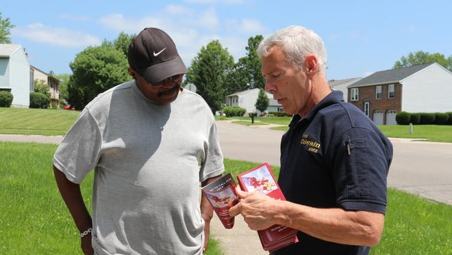 Colerain Township resident Ron Pierce talks with Colerain Township Firefighter/Paramedic Phil Klug about a new information brochure on drug overdoses that township officials hope will help save lives. Township officials hope to eventually take the brochures to every residence in the township.
