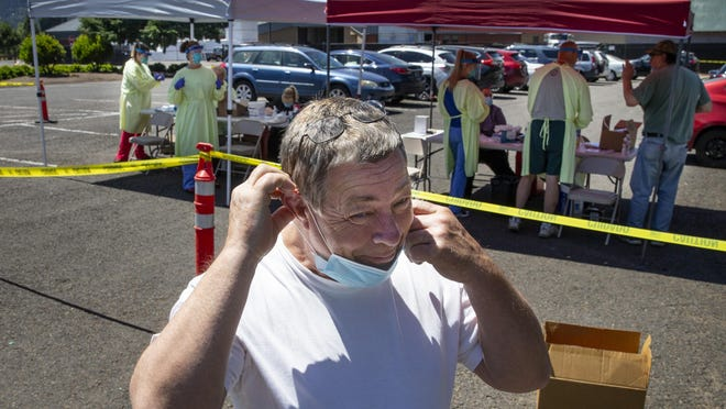 With his eyes still watering, Kye Robson puts his mask back over his face after receiving a COVID-19 test during an outdoor testing opportunity for front-line workers at the Lane County Fairgrounds in Eugene. [Chris Pietsch/The Register-Guard] - registerguard.com