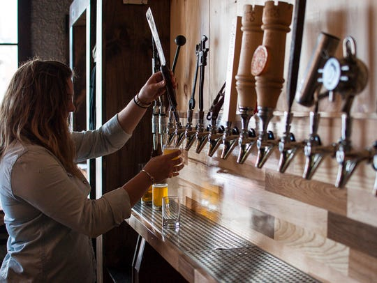 Eliza Benton pulls a sample for a flight of beers at