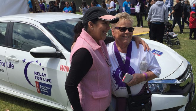 Felicia Kausin, left, hugs Marilyn Moore whose son, Jaime, won the 2016 Honda Civic at Relay for Life Salinas