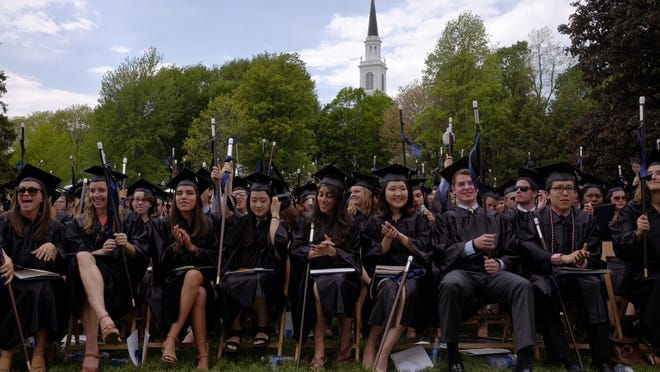 Middlebury graduates wave their canes in the air during the college's commencement ceremony on Sunday. After getting their diplomas, they each received a cane, which is a replica of the cane left to the college by one of its founders, Gamaliel Painter. The original hangs in the president's office.