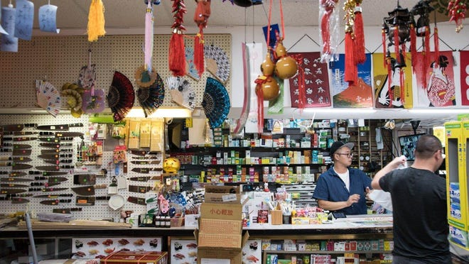 Owner Geoffrey Yao rings up a customer at his Fortune Cookie market in West Palm. The market draws a mix of chefs and home cooks, and it isn't unusual for customers to trade tips and knowledge about different dishes and ingredients.