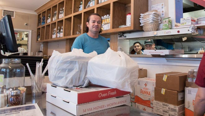 Javier Gonzalez, manager of Pizza al Fresco in Palm Beach, expedites pickup and delivery orders. During the coronavirus shutdown, the restaurant is offering free delivery to island residents, from Sloan's Curve to the inlet.